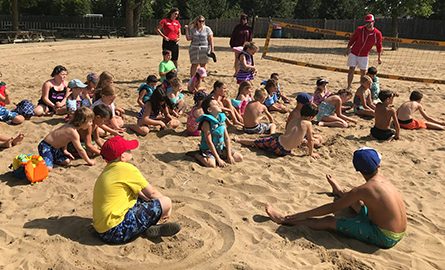Kids sitting on the sand listening to a camp counsellor